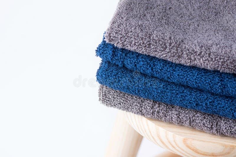 Сложенный washcloth полотенец Terry хлопка на деревянном стуле на белой предпосылке Забота тела материалов многоразового eco прач стоковое изображение
