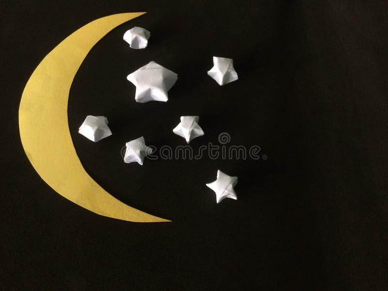Сложите звезду белой бумаги и отрежьте серповидную луну стоковое фото