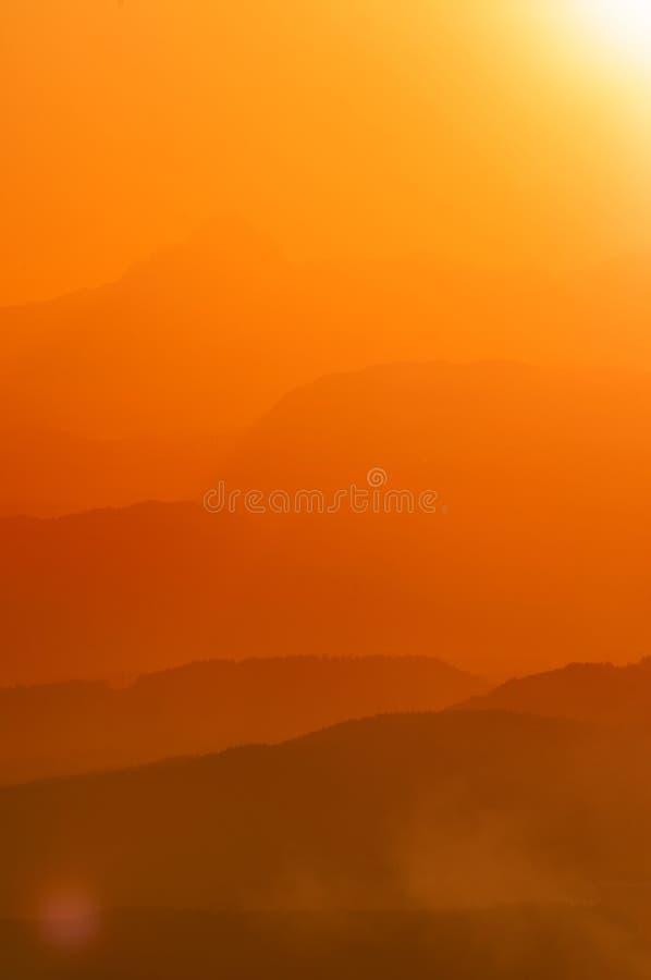 Слои холмов и гор в красивом оранжевом излучающем свете заходящего солнца стоковые фотографии rf