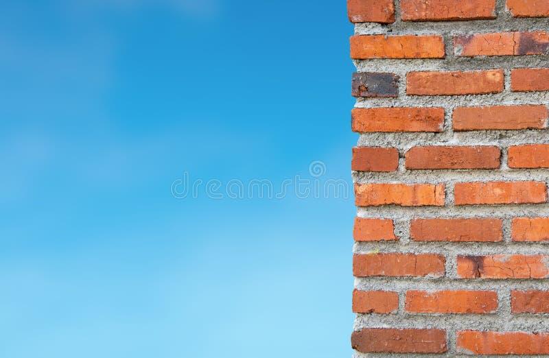 Слой красной кирпичной стены здания против голубого неба Выведенную часть можно использовать как космос экземпляра или положила с стоковые изображения