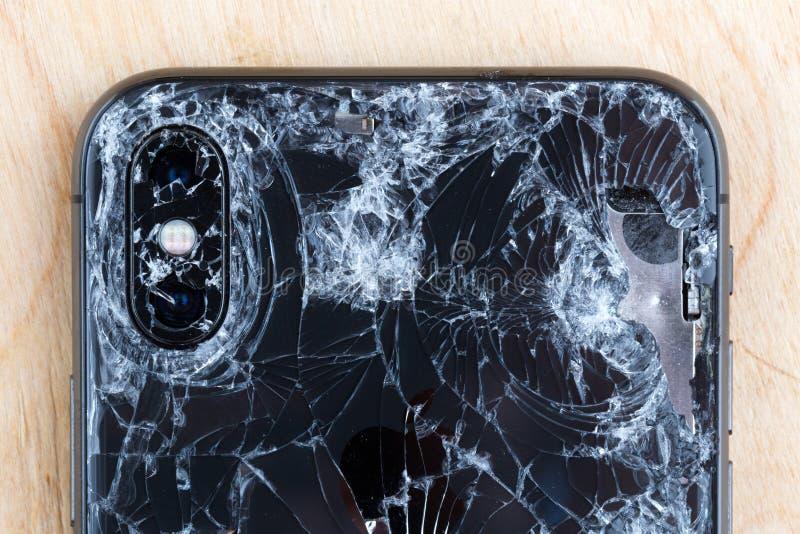 Сломанное iPhone XS лежит на деревянной поверхности стоковое фото rf