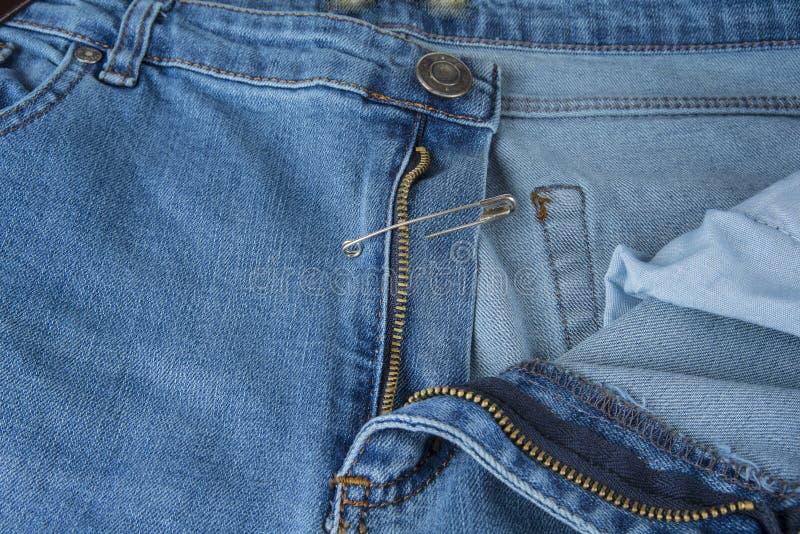 Сломленная молния голубых джинсов зафиксированная с английской булавкой стоковые фотографии rf