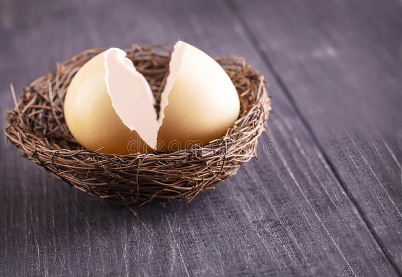 Сломленные раковины яйца в гнезде на старой деревянной предпосылке стоковые фотографии rf
