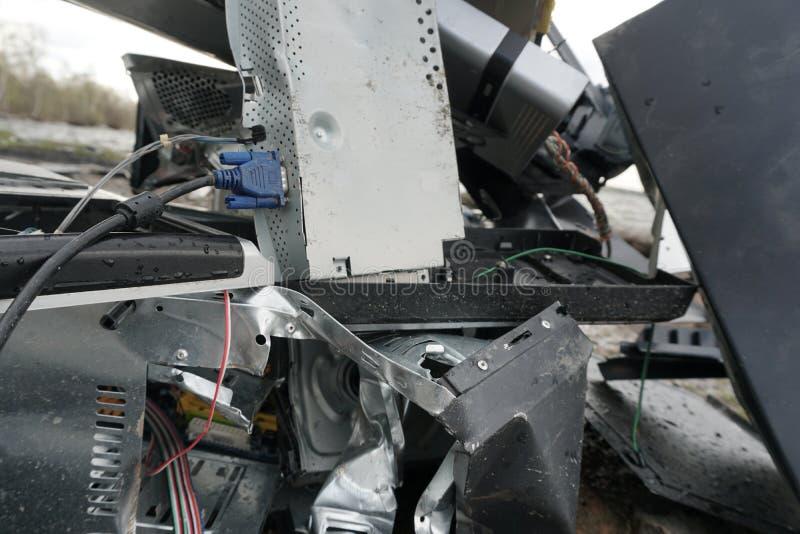 Сломленные части, мониторы и принтеры компьютера перед ландшафтом природы с предпосылкой реки Сброшенное электронное стоковая фотография rf