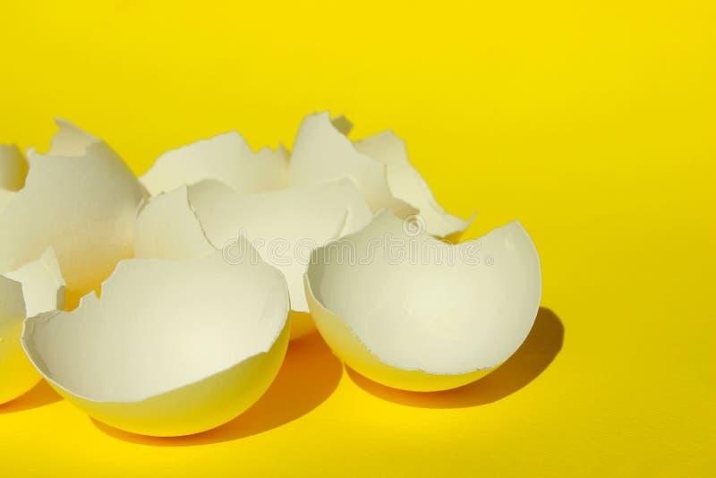 Сломленный белый Eggshell цыпленка Белый Eggshell над желтой предпосылкой Красочная предпосылка стоковые фото
