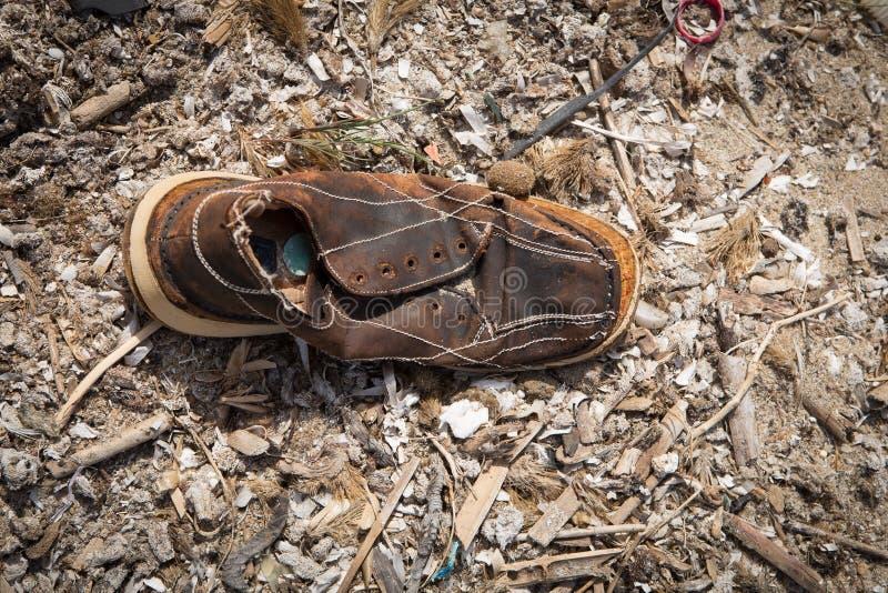 Сломленный ботинок лежа на пляже стоковая фотография