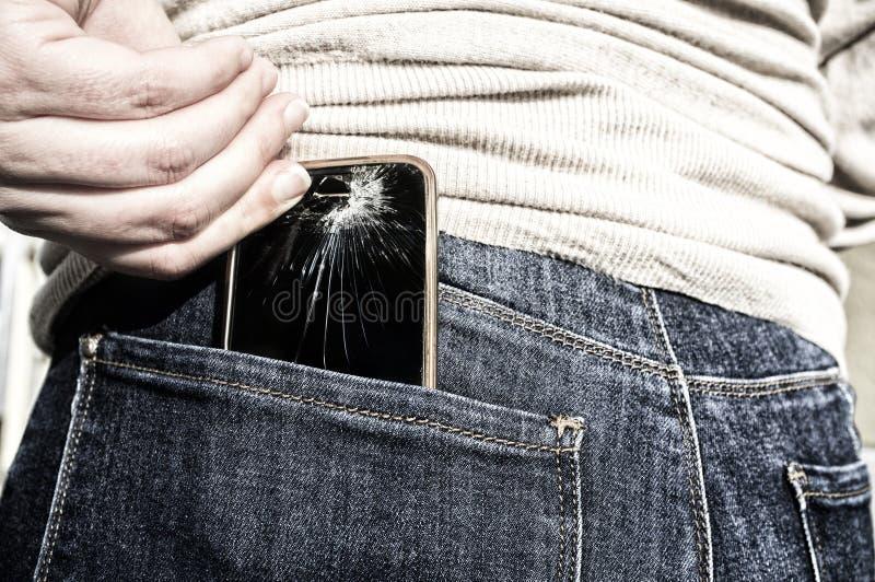 Сломленный мобильный телефон вверх от ее карманных джинсов задыхается после сидеть стоковое фото