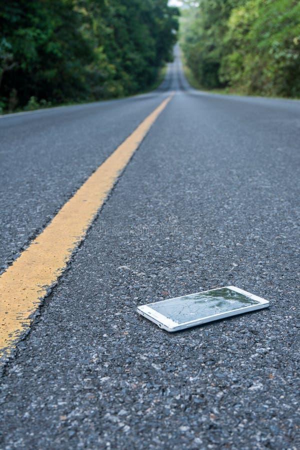 Сломленный новый Smartphone на дороге асфальта в лесе кто-то упал прибор Отказы на большом дисплее стоковые изображения