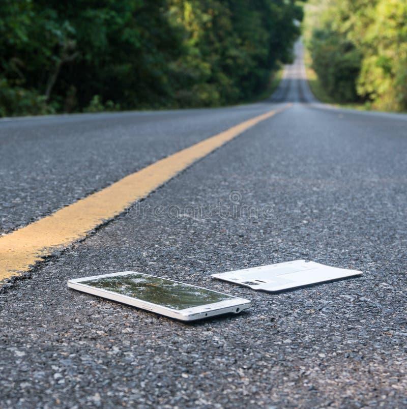 Сломленный новый Smartphone на дороге асфальта в лесе кто-то упал прибор Отказы на большом дисплее стоковое фото rf