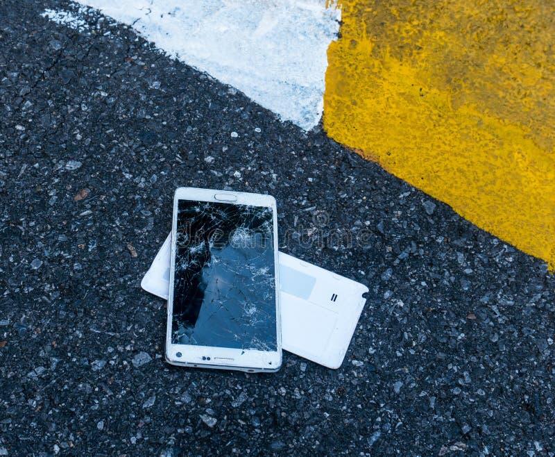 Сломленный новый Smartphone на дороге асфальта Кто-то упало прибор Отказы на большом дисплее стоковая фотография rf