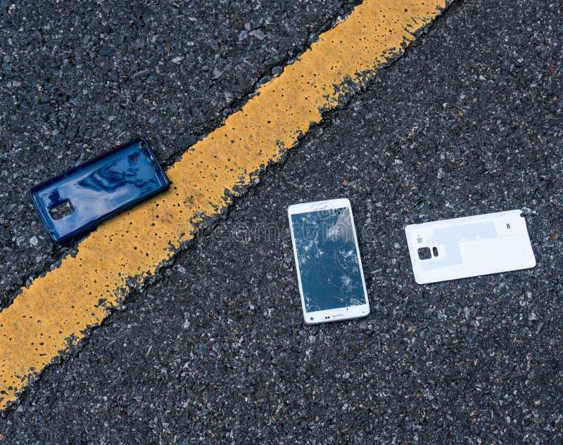 Сломленный новый Smartphone на дороге асфальта Кто-то упало прибор Отказы на большом дисплее стоковые изображения