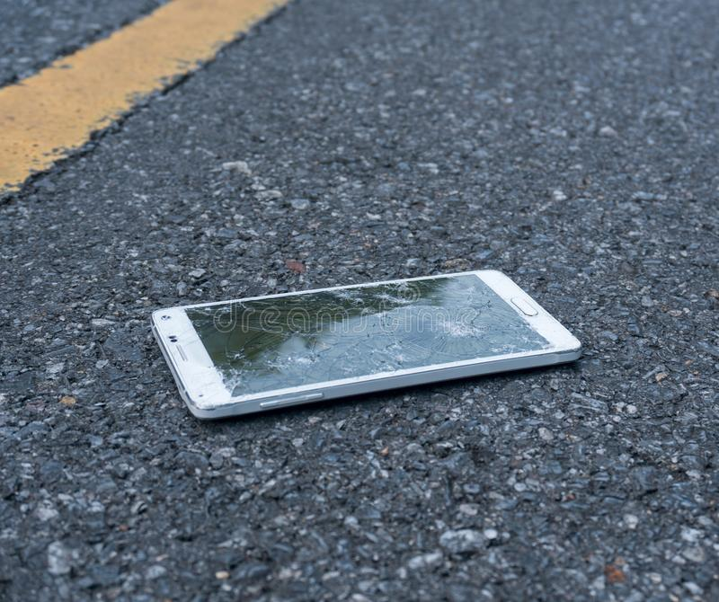 Сломленный новый Smartphone на дороге асфальта Кто-то упало прибор Отказы на большом дисплее стоковое фото rf