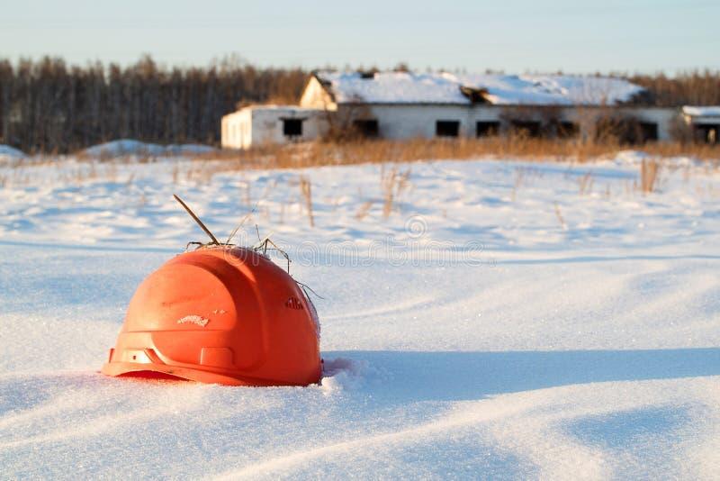 Сломленный оранжевый шлем конструкции на предпосылке загубленного здания в сугробе стоковые фото