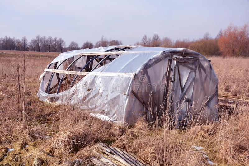 Сломленный покинутый пластичный парник в предыдущей весне стоковое фото