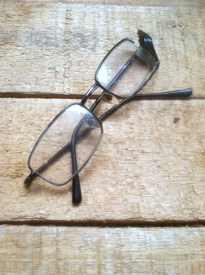 Сломленный eyeglass на деревянной доске стоковые изображения rf