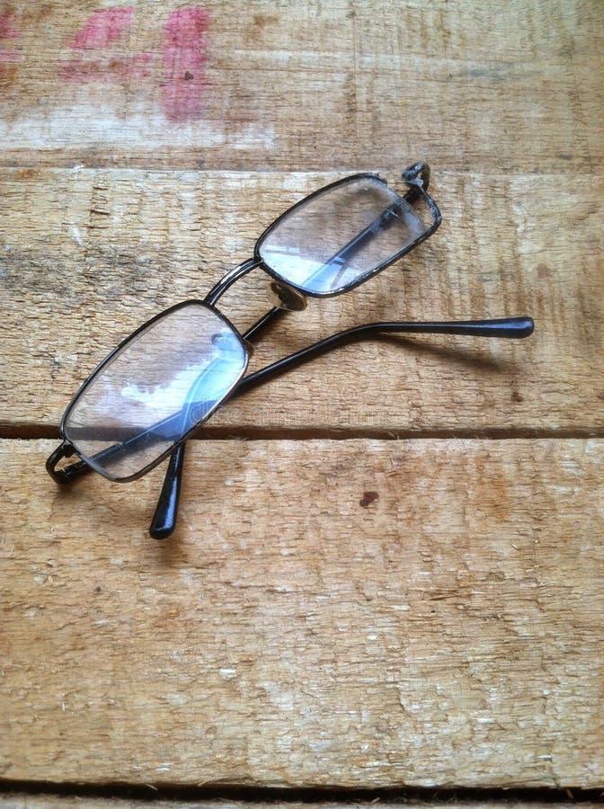 Сломленный eyeglass на деревянной доске стоковое изображение