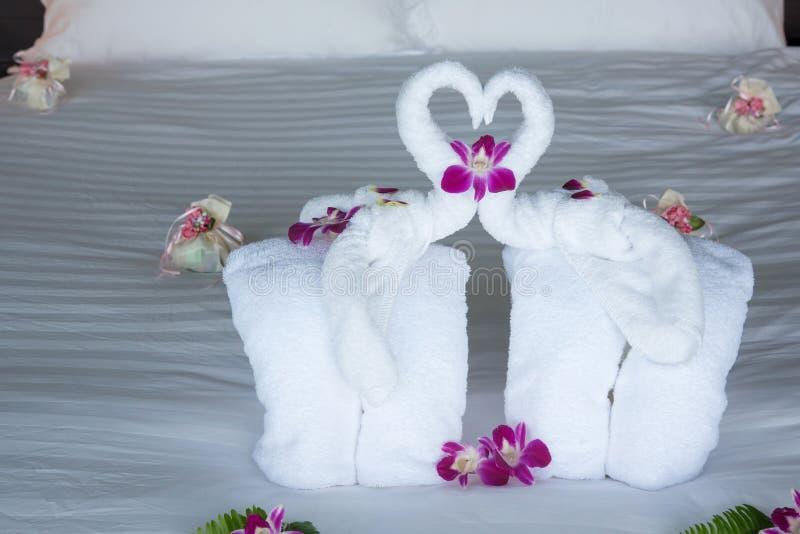 Слон 2 и сердце сделанные от полотенец на медовом месяце кладут в постель стоковая фотография rf