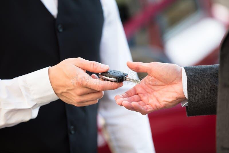 Слуга давая ключ автомобиля к предпринимателю стоковые фотографии rf