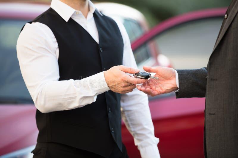 Слуга давая ключ автомобиля к предпринимателю стоковое фото rf