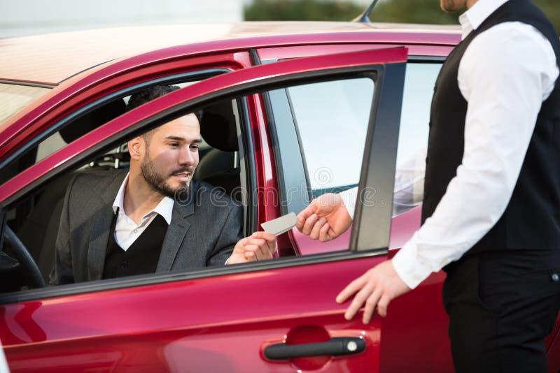Слуга давая получение к предпринимателю сидя внутри автомобиля стоковые фото