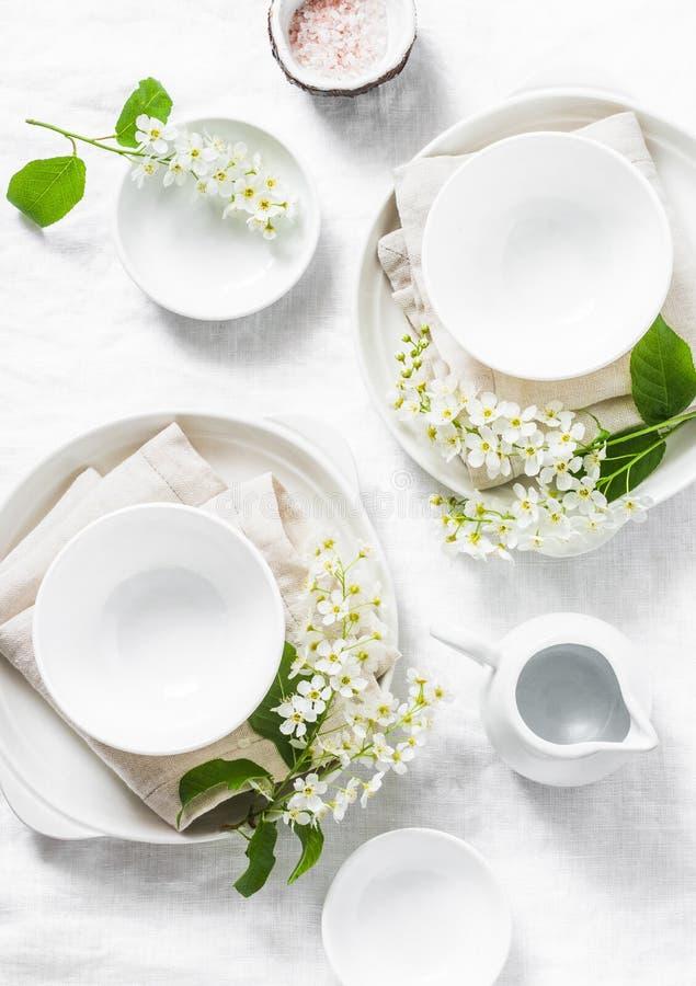 Служат пустая таблица с белой посудой, цветками, салфетками на белой предпосылке, взгляд сверху Уютная домашняя таблица еды серви стоковое фото