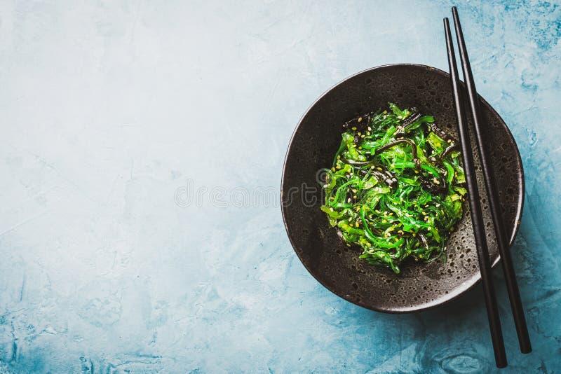 Служат салат морской водоросли, который и подготавливает для еды стоковое фото