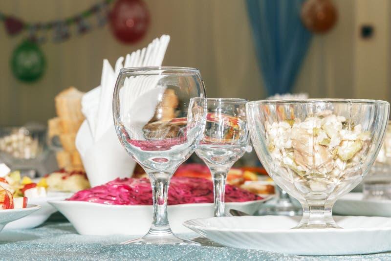 Служат таблица банкета с запачканной предпосылкой в ресторане Пустые бокалы, салат овощей и отрезанный крупный план плодоовощ Сто стоковое изображение rf