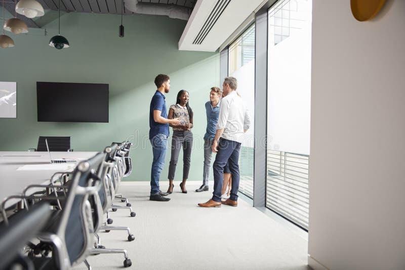 Случайно одетые бизнесмены и коммерсантки имея неофициальное заседание в современном зале заседаний правления стоковое фото