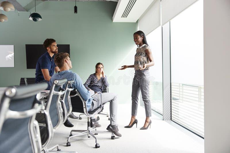 Случайно одетые бизнесмены и коммерсантки имея неофициальное заседание в современном зале заседаний правления стоковая фотография