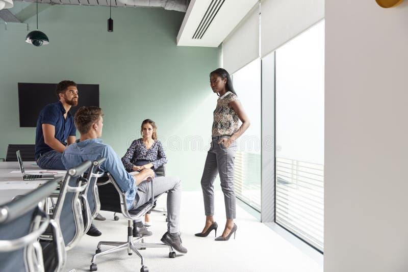 Случайно одетые бизнесмены и коммерсантки имея неофициальное заседание в современном зале заседаний правления стоковые фото