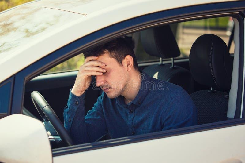 Случайный молодой водитель парня испытывая головную боль, должен остановить автомобиль после управлять в заторе движения стоковое фото