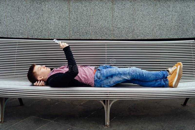 Случайный молодой человек в рубашке и куртке шотландки лежа outdoors Студент используя смартфон лежа на стенде в городе стоковое фото rf