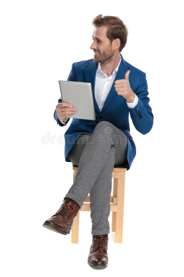 Случайный парень давая большой палец руки вверх и держа его планшет стоковое изображение