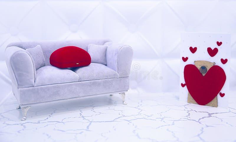Случай на праздник, свадьба ювелирных изделий, захват на декоративной софе с картой в сердцах, подарком к невесте, женщине, красн стоковое фото