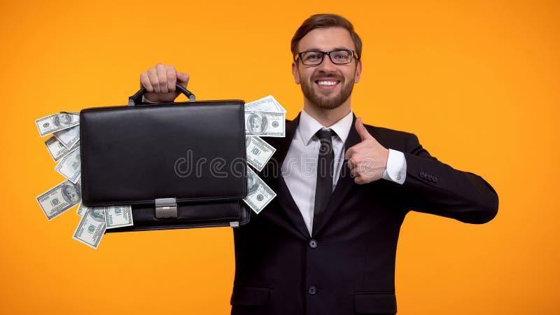 Случай показа человека упакованный с деньгами, делая большие пальцы руки-вверх, заем, легкий кредитовать стоковая фотография