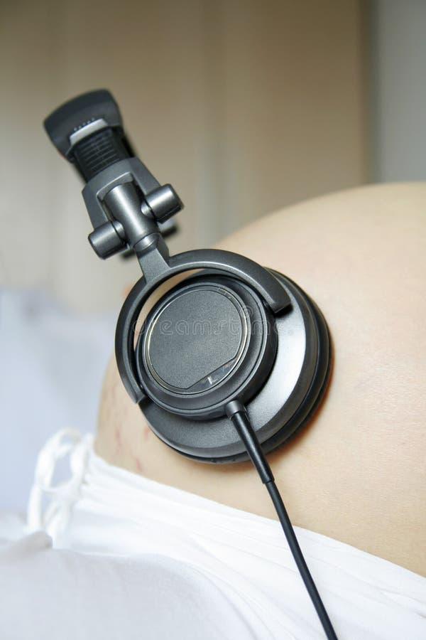 слушают беременные женщины нот стоковое фото