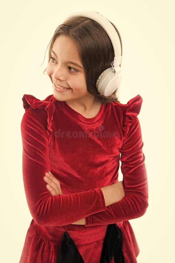 Слушают бесплатно новые и предстоящие популярные песни прямо сейчас Музыка всегда со мной Маленькая девочка слушает радиотелеграф стоковое фото rf