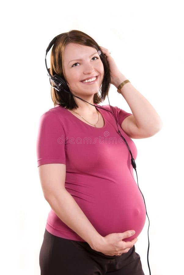 слушая нот супоросое к женщине стоковая фотография