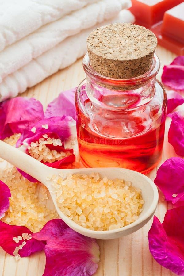 Смажьте в стеклянной бутылке, соли моря, полотенце и лепестках розы стоковая фотография