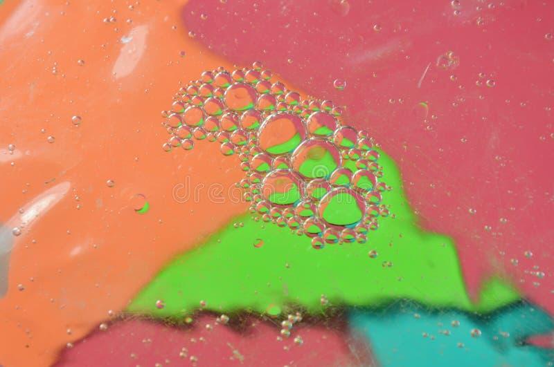 Смажьте пузырь плавая на поверхность воды в предпосылке цвета стоковое изображение