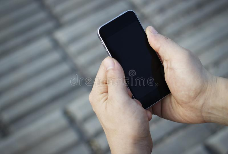 Смартфон в мужских руках, взгляд сверху, outdoors стоковая фотография rf