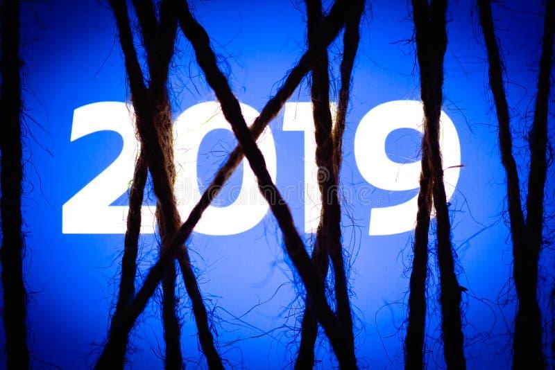 Смартфон в темноте, плотно в оболочке и связанной с грубой кабалой веревочки джута лежит с накаляя голубым экраном с текстом 2019 стоковое фото rf