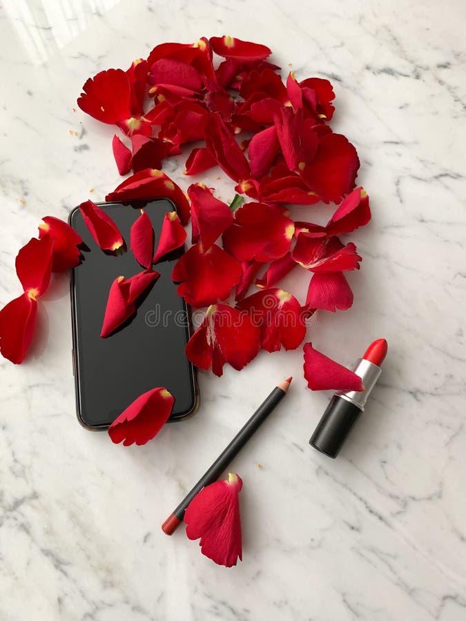 Смартфон в цвете стиля iphone черном с лепестками красной розы и красной губной помадой на мраморной предпосылке столешницы, взгл стоковые фотографии rf