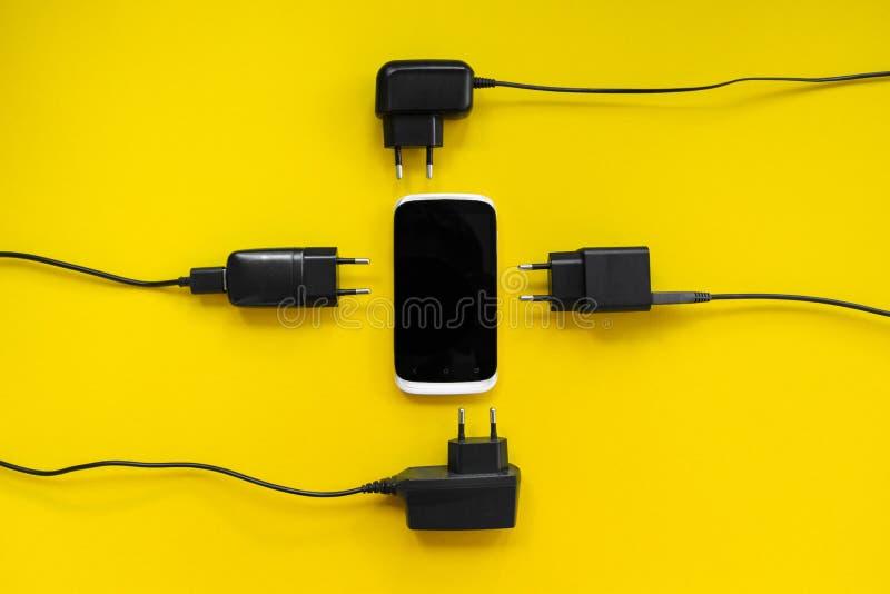 Смартфон и заряжатели вокруг на желтой предпосылке, концепции стоковое изображение