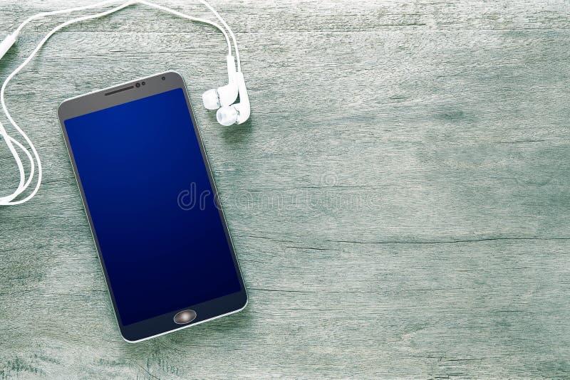 Смартфон и наушник на предпосылке винтажного grunge деревянной стоковые фото