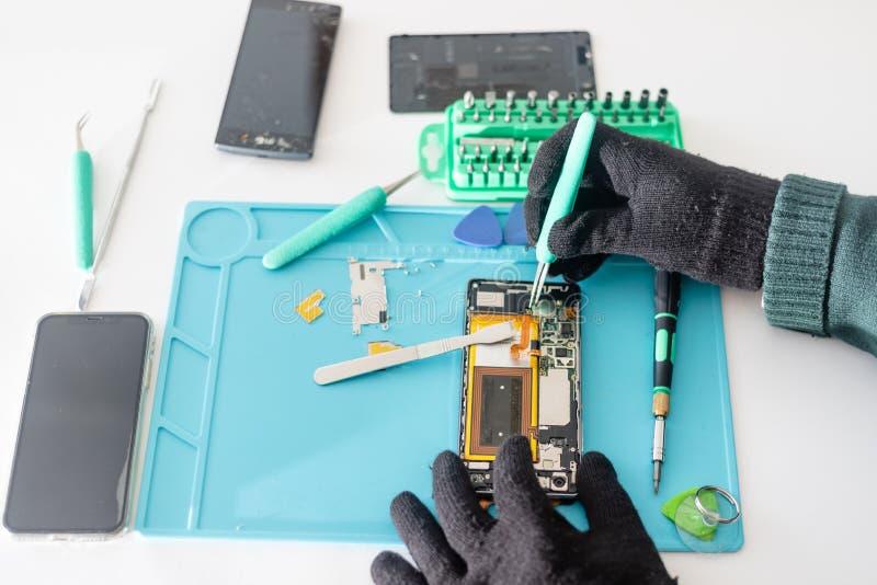 Смартфон компонентов техника или инженера демонтируя сломленный и принять с доски логики для ремонта или заменить новый смартфон стоковое фото rf