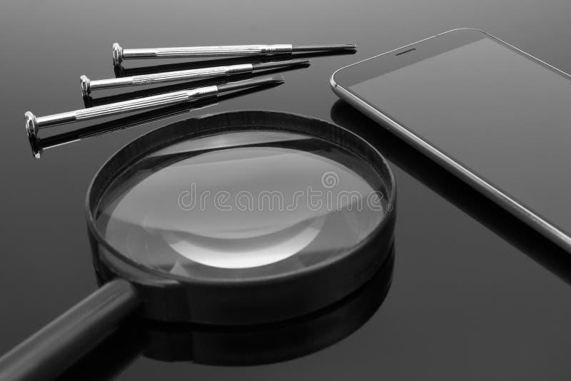 Смартфон, отвертка и увеличитель на темной поверхности зеркала стоковое фото