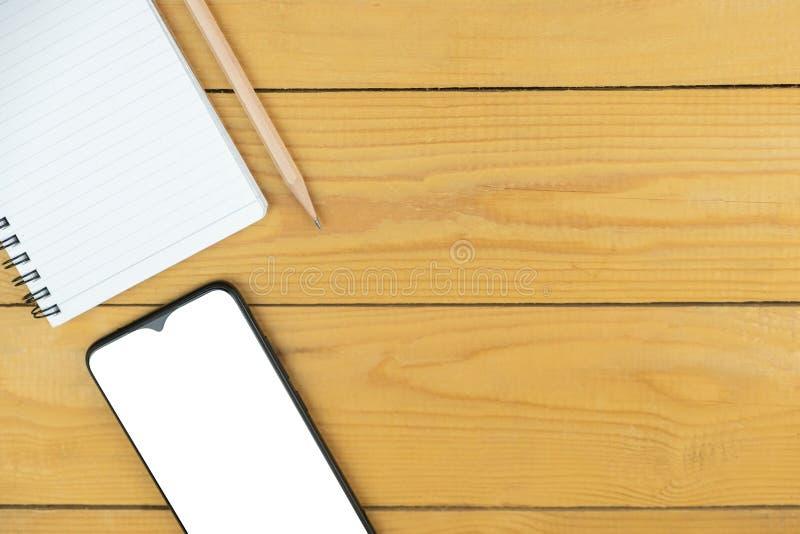 смартфон, пустая блокнот и карандаш на столе, макет на экране, копирование пространства стоковые фото