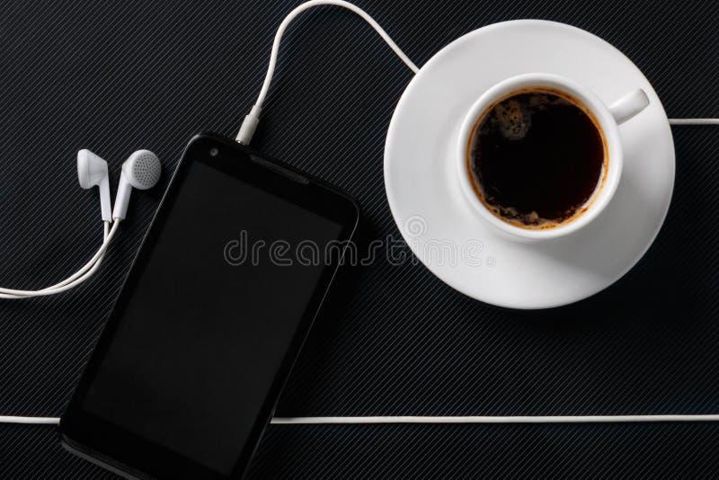 Смартфон с наушниками и чашкой кофе на черной текстурированной поверхности Плоское положение стоковое фото