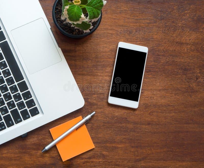 Смартфон с пустыми черными экраном и частью клавиатуры ноутбука на деревянном столе стоковое фото rf